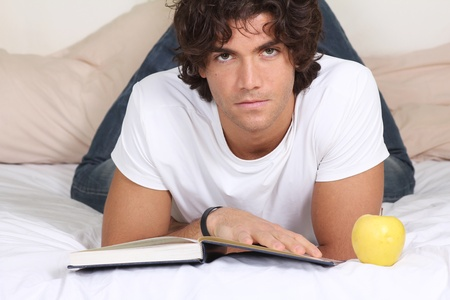 Attractive  young man read a book and relax on bed photo