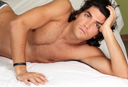 Handsome and sexy young man on bed  Stock Photo