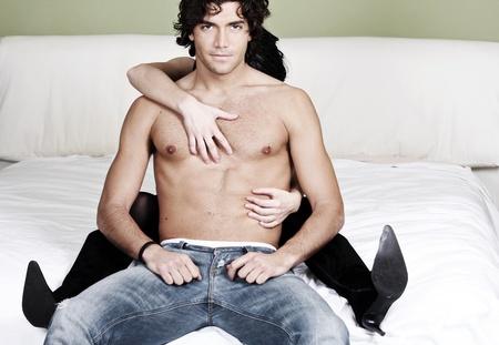 sexualidad: Joven, atractiva y sexy con una expresión inteligente se lleva a cabo en un abrazo posesivo