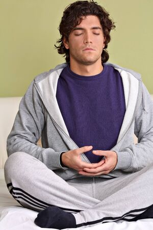 Young man meditating in lotus position at home photo