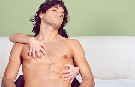sexualidad: Joven sexy a cabo en un abrazo posesivo. Mirada audaz a la cámara. Pasión concepto. Foto de archivo