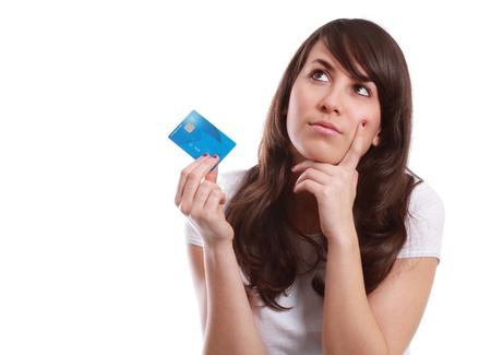 Young girl is thinking about her next purchase with a credit card in hand. White background. Stock Photo - 12472668