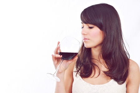 Attractive young girl looking at red wine glass on white background. Stock Photo - 12472694