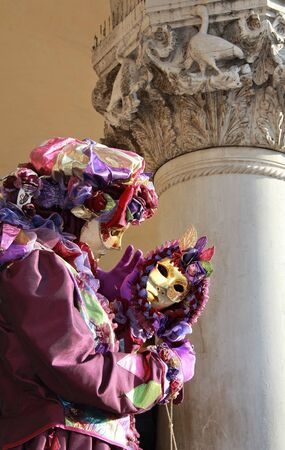 Purple dressed joker mask reflected in a mirror under a classic marble column. 2012 Venice Carnival. photo