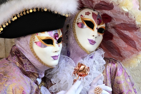 Noble and elegant couple masked in rich velvet and silk  dresses . Copper rose and floral hat. 2012 Venice Carnival.