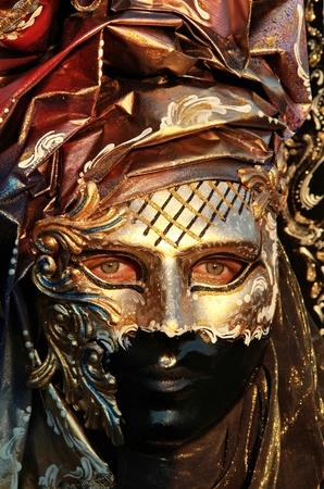 Rich golden mask detail in sunset light. 2012 Venice Carnival . photo