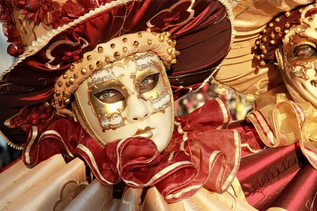 Close up of a colourful mask in gold and red with music score on it.  2012 Venice Carnival.
