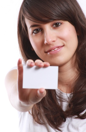 Smiling young girl showing blank business card in hand. Against white background . Stock Photo - 12473691