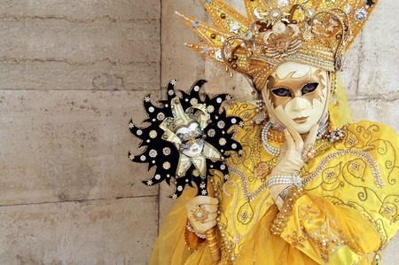 A yellow crowned mask against stone background . 2012 Venice Carnival
