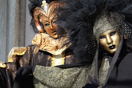 Venetian masked couple .Bronze and golden masks . Focus and detail  on lady  . 2012 Venice Carnival.