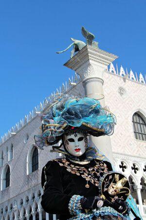 leon alado: Cian m�scara veneciana con sombrero bajo el pilar plaza San Marco. Le�n alado es simbol de Venecia. 2012 Carnaval.