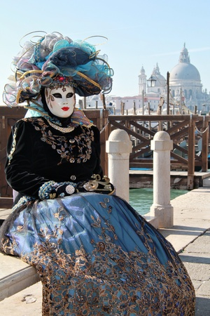 Cyan lady mask with hat at gondola pier . Cathedral in background . 2012 Venice Carnival photo