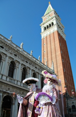 Elegant and noble masked couple under Bell tower of San Marco   Venice Carnival  2012  Stock Photo - 12468529