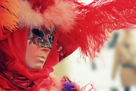Red venetian mask portrait with feathers . 2012 Venice carnival . Retro effect   photo