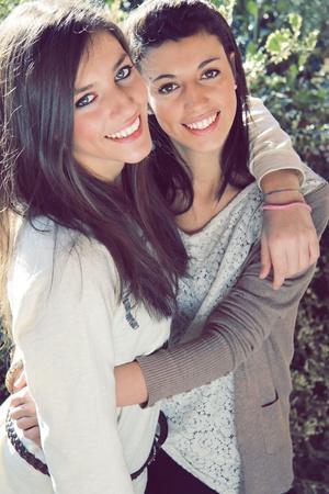 Due giovani sorelle sorridenti abbracciato la luce esterna e naturale
