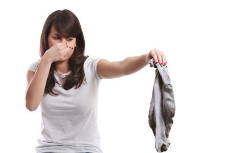 stink: Young girl disgusted expression for stinking socks   On white   Bad smell concept Stock Photo