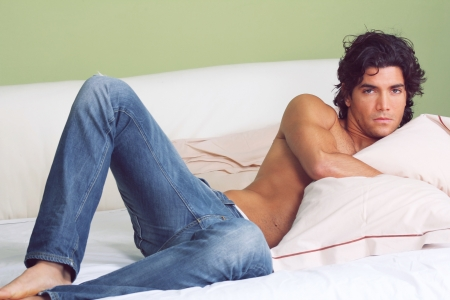 Young handsome man shirtless , embraced to pillow ,  in a sensual pose on bed.  photo