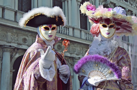 Beautiful noble couple in elegant silk dress  . Man is calling with finger gesture .Venice carnival 2012 . Stock Photo