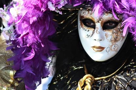 豊富な羽の紫色のマスクの肖像画のヴェネツィアのカーニバル 2012