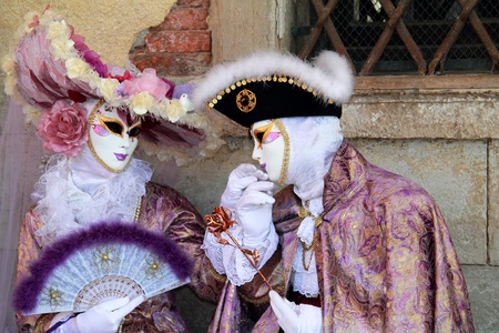 Elegant noble couple masked at Venice carnival 2012   Man is kissing lady Stock Photo