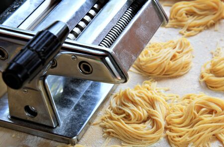 Manual pasta maker with fresh egg homemade tagliatelle . Healthy food concept photo