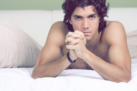 Intense gaze at the camera from handsome and sexy guy lying on sheets  Stock Photo - 12797838