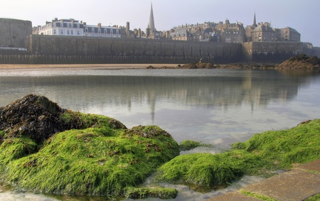fortify: Saint Malo, pirate walled city from low tide beach . Brittany , France