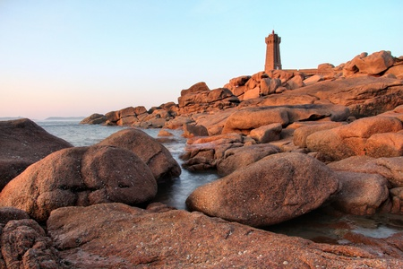 Men Ruz Lighthouse in Ploumanach at sunset , cote du granit rose , Brittany in France .