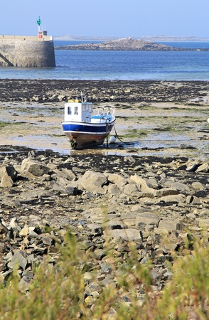 Boat is stacked in low tide hours. Roscoff bay , Brittany , France photo