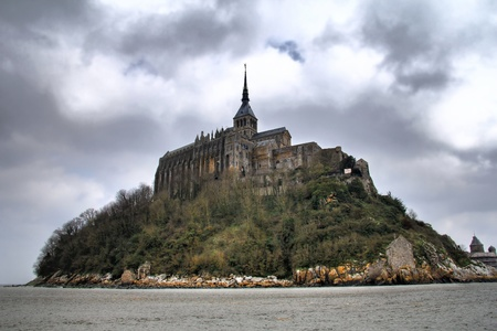 Mont Saint Michel backside with dramatic cloudy sky. Normandy , France