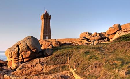 granit: Sunset light on Men Ruz Lighthouse in Ploumanach. Cote du granit rose , Brittany in France .