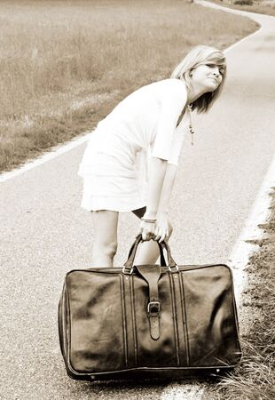 Cool young girl is pulling an old heavy suitcase on a country road with funny expression  photo