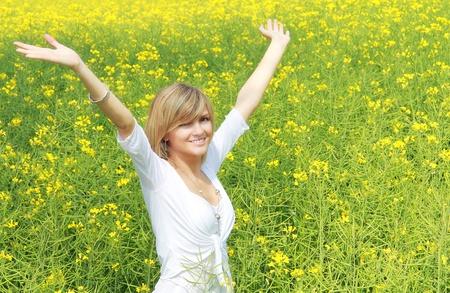 Gelukkig en lachende meisje in tha midden van een gele bloem veld Natuurlijk licht vrijheid begrip Stockfoto