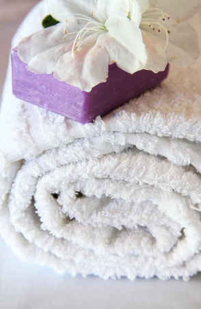 cleaness: Toiletries and spa composition with white flower , purple soap bar and towel . Cleaness concept