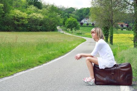 mujer con maleta: Buena chica está esperando en una maleta en la frontera de un camino rural. Viajes conceptual