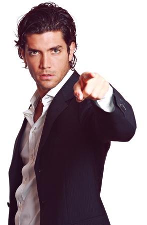 セクシーなエレガントな若い男はカメラに指を指しています。ファッション スタジオ ショットします。白で隔離されます。 写真素材