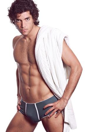 homme nu: Sexy jeune homme musclé avec des sous-vêtements gris et une serviette blanche. Isolé sur fond blanc