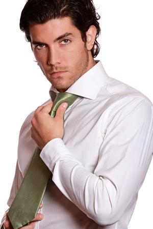 Aantrekkelijke zakenman tot vaststelling van zijn elegante groene stropdas. Succes conceptuele. Studio shot op wit wordt geïsoleerd. Stockfoto