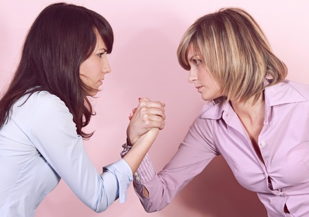 Two determined young girls arm wrestling. Disagreement concept. photo