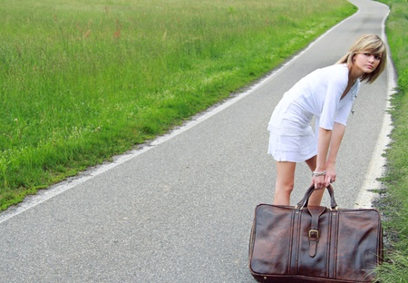 Cool young girl is pulling an old heavy suitcase on a country road . photo