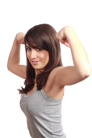 Pretty young girl showing her biceps . Isolated on white.