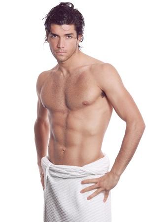 hombre desnudo: Sexy joven musculoso con el pecho desnudo y una toalla blanca. Aislado en blanco Foto de archivo