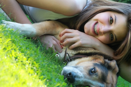 Close portrait of young girl hugged to her dog on the grass. Frendship concept. photo