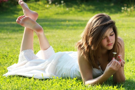 Pretty young girl is tearing petals from a daisy , lying on grass with bare feet. Love conceptual photo