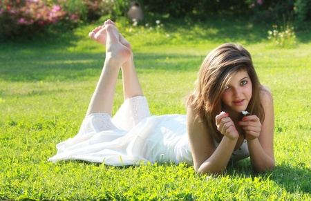 bare feet girl: Pretty young girl  lying on grass with bare feet. Model looks at camera