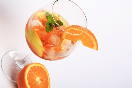 Alcoholic fruit cocktail with lemon , orange , aperol and mint leaves as decoration. Elegant glass
