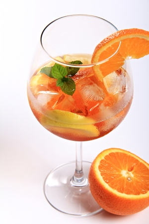 Elegant glass of  a fruit cocktail with lemon , orange and aperol . Mint leaves as decoration.