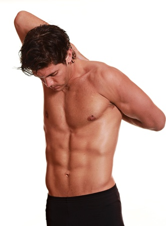 toning: Young man stretching his arms behind the back . Fitness and workout concept