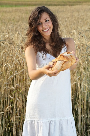 Beautiful and smiling girl offering  bread in her hands . Wheat field as background photo