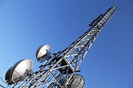 Diagonal view of a broadcasting metal tower against blue sky Standard-Bild